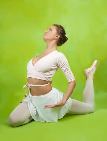 Young female ballerina  performing a dance over green background  photo