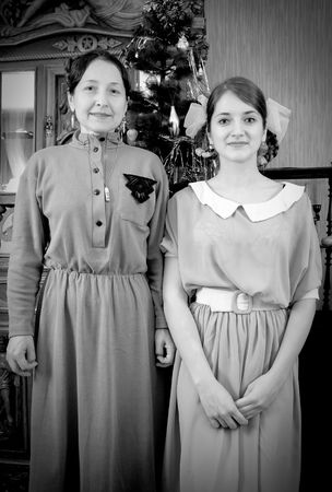 Vintage photo of daughter with mother against Christmas tree at home Stock Photo - 6499255