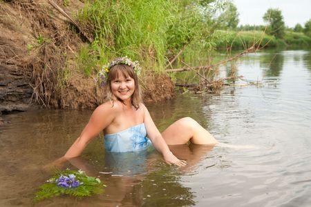 undine: Blonde girl  in flower chaplet at river