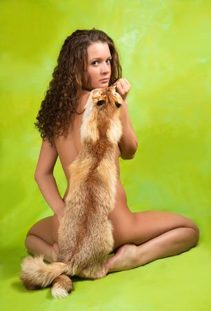 Rear view of a naked curly  girl  with fox fur over green Stock Photo - 6529255
