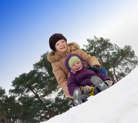 mother with little child sliding in the snow against winter park  photo