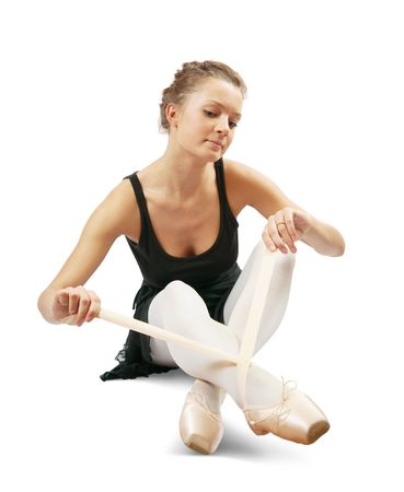pointes:  Ballerina putting on pointes. Isolated over white background