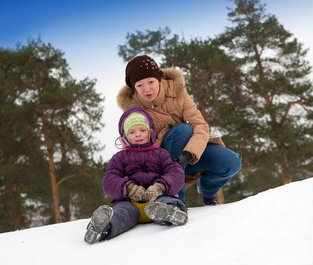 Young girl riding in a city park with a snow slide.  photo
