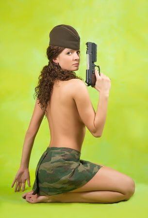 Sexy military woman with gun over green background photo