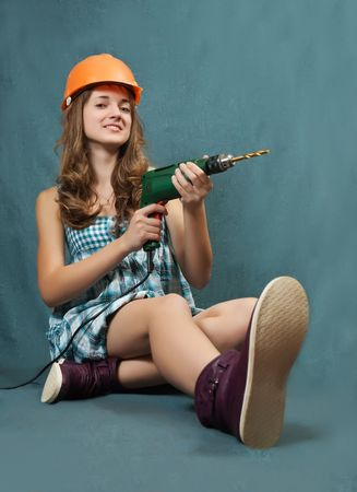 Female construction worker in a hard hat with drill over grey background photo