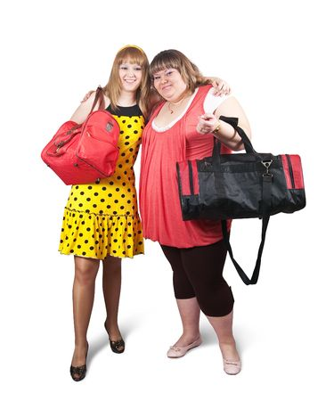 meagre: Two happy casual girls with travelling bags over white background Stock Photo