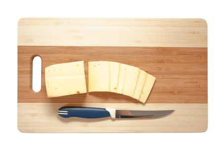 Chefs knife hopping an cheese on an wooden cutting board - white background. photo