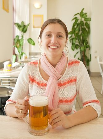 Beautiful woman relaxing at bar with a beer photo