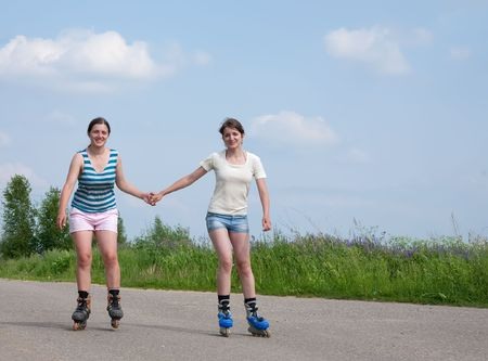 Two young females rollerskating on asphal road photo