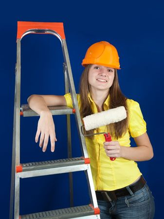 scaling ladder: female house painter with paint rollers near scaling-ladder