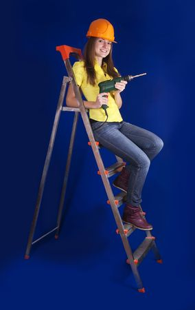 Girl in a hard hat with drill on stepladder photo