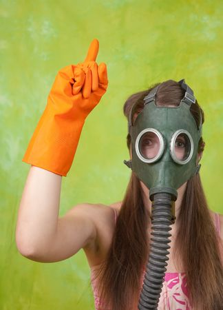 stop pollution: girl in gas mask pointing ATTENTION! over green background