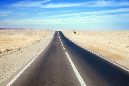 lane lines: Road through desert landscape under cloudy sky