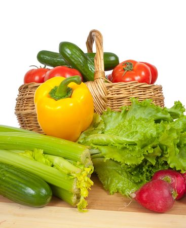 Ripe vegetables in basket on white background photo