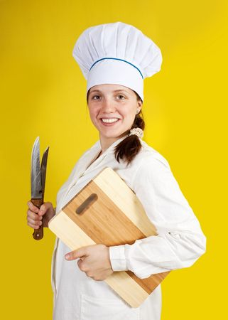 Portrait of female cook with  cutting board over yellow  photo