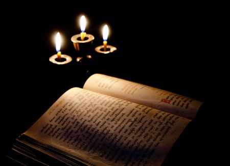 old Psalter and candles in candelabrum against black Stock Photo - 6782134