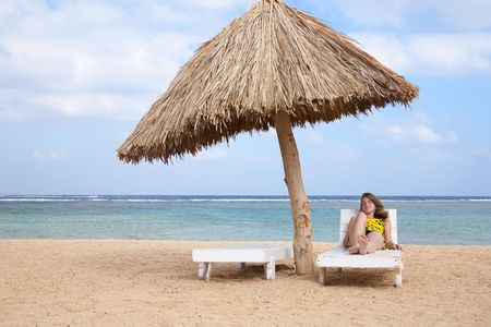 beauty girl relaxing in deck chair at resort beach photo