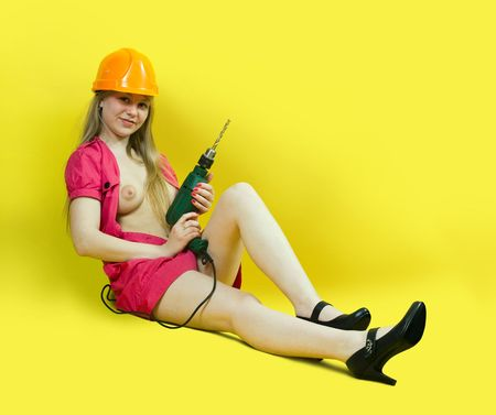 Sexy girl with drill over yellow background