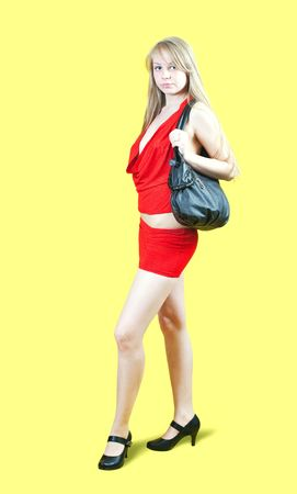 Attractive young woman with handbag standing on yellow background