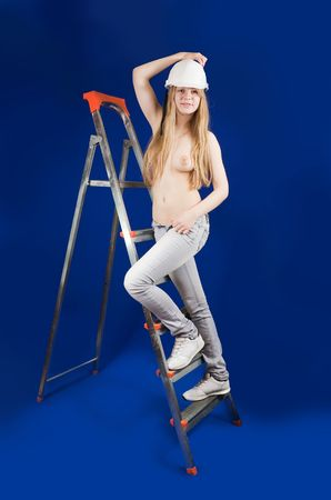 Topless girl in hard hat on stepladder over blue photo