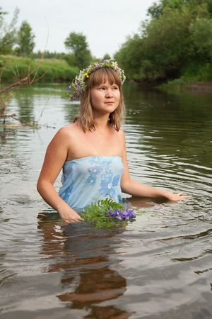 Blonde girl  in flower chaplet at river photo