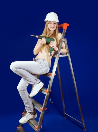 Topless girl  with drill on scaling-ladder over blue photo