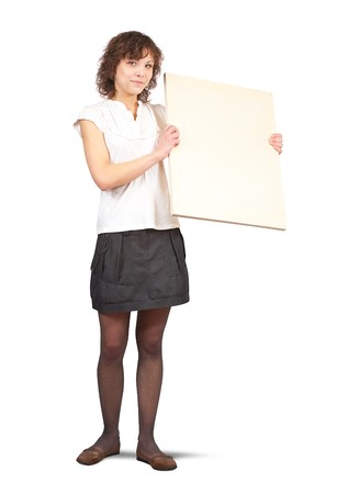 Standing curly girl holds empty poster over white photo