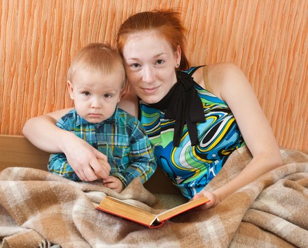mother with her son   reading book on sofa Stock Photo - 6877477