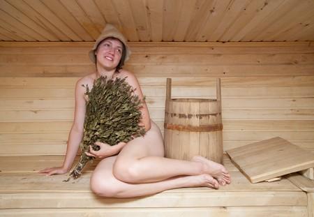 sauna nackt: nackte junge Frau sitzt auf einer Bank in einer sauna  Lizenzfreie Bilder