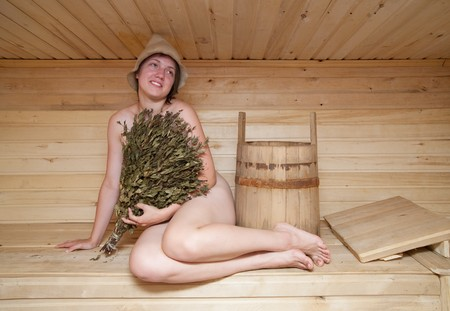 naked Young woman sits on a bench in a sauna photo
