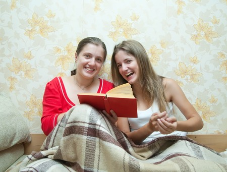 two happy girls sitting in the bed and reading a book together  photo