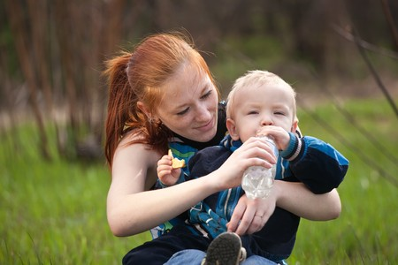 mother with son drinking water on meadow photo