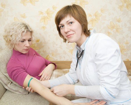 Doctor giving a girl an intravenous injection in her arm photo