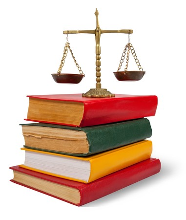justice balance:  Scales of justice atop legal books over white