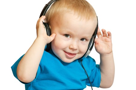 Little nice boy listening to music with peaceful expression on face photo