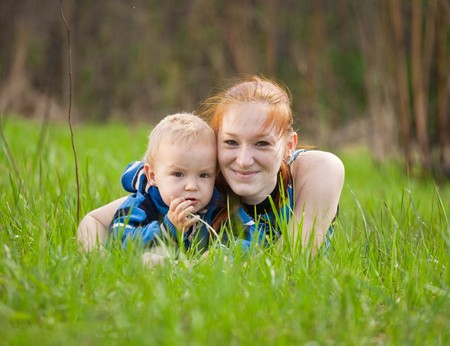 Happy mother with her son on meadow photo