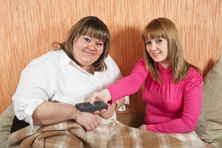 Young women smiling with TV remote control photo