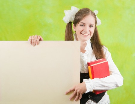 long-haired schoolgirl holds blank canvas over green  photo