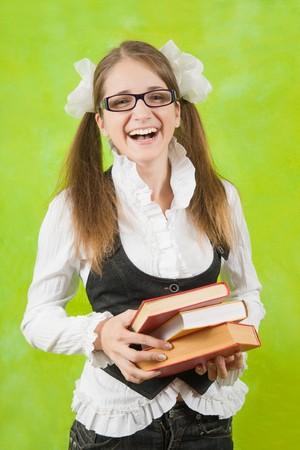 teener: Happy schoolgirl in glasses with books over green background