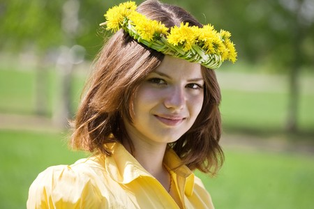 chaplet: brunette girl in dandelion chaplet against nature