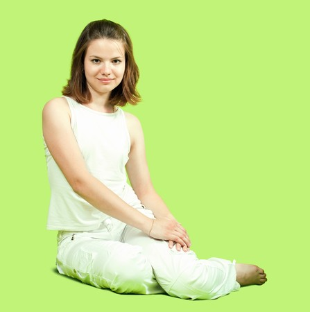 teenager girl in white sitting on green background photo