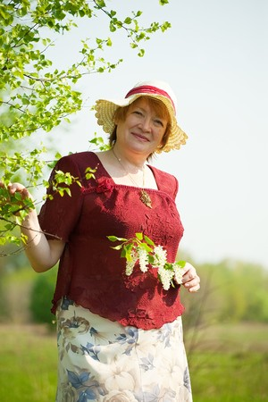 senior woman  in  hat at spring  meadow photo