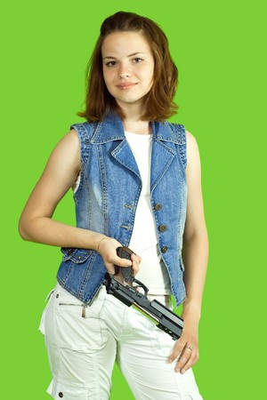 Pretty girl in white with gun on green background Stock Photo - 6986602