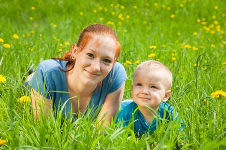 Mother and son laying on the green grass photo