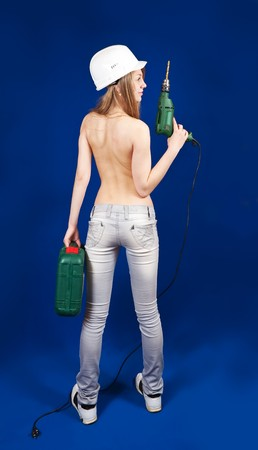 Rear view of  Topless girl in hard hat with tool box  and drill over blue photo