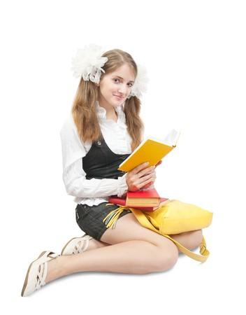 school uniform girl: Sitting schoolgirl reading book, isolated over white