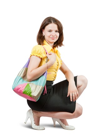 Attractive young girl with handbag sitting on white background