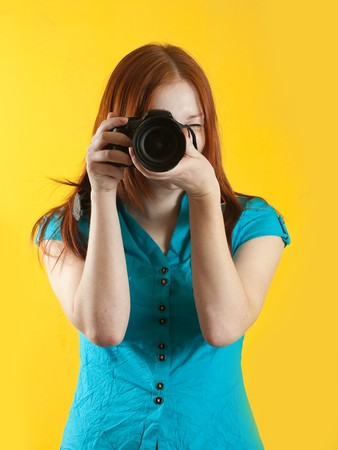 Young female photographer with camera over yellow background Stock Photo