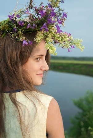 horizont: long-haired teen girl  in flower chaplet against river Stock Photo
