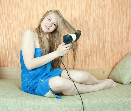 Girl using hairdryer and comb in home interior photo